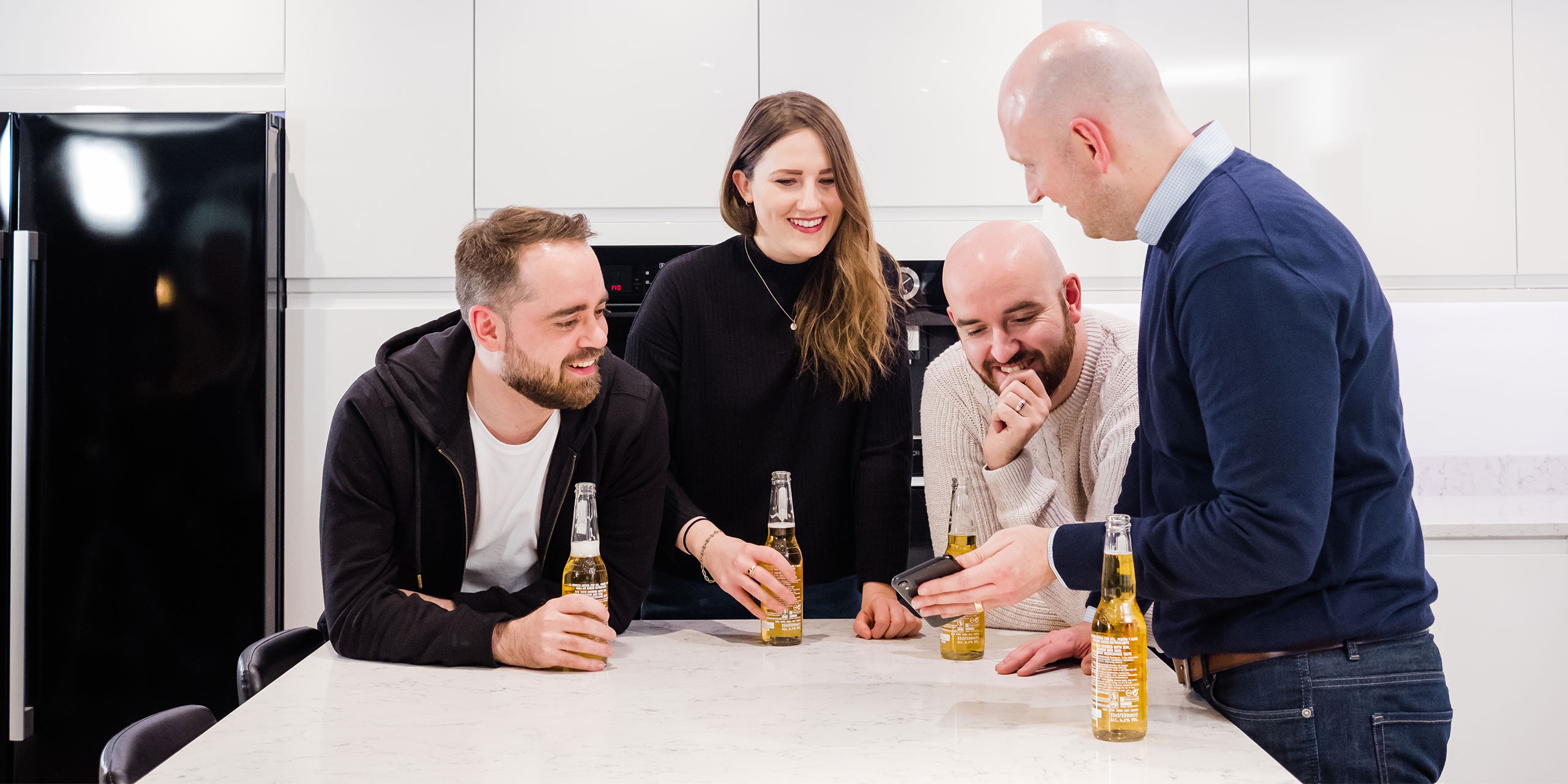 Hosting group of people drinking in a white kitchen and laughing
